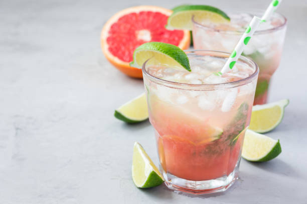 cold pink cocktail with fresh grapefruit, lime and ice cubes on concrete background, paloma, copy space - grapefruit cocktail stock photos and pictures