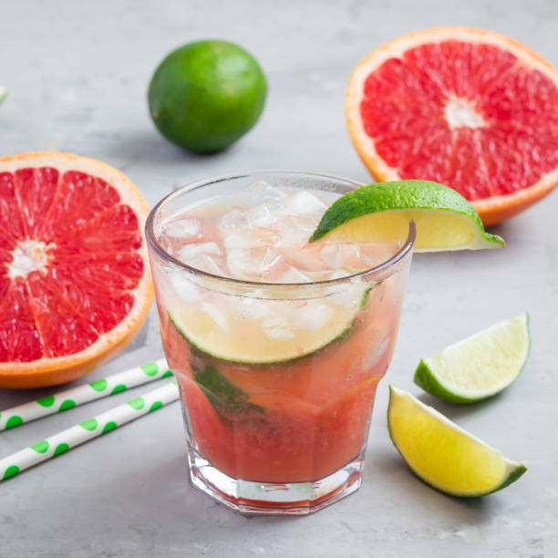 cold pink cocktail with fresh grapefruit, lime and ice cubes on concrete background, paloma, square - grapefruit cocktail stock photos and pictures