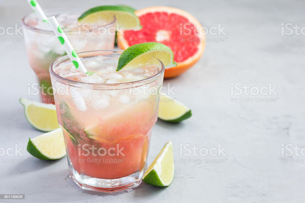 Cold pink cocktail with fresh grapefruit, lime, copy space stock photo