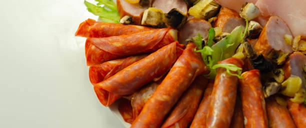 Um prato frio preparado para a festa com chorizo fatiado, presunto e salsichas, - foto de acervo