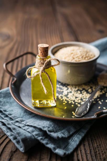 huile de sésame pressée à froid dans une bouteille en verre et graines dans un bol - cold pressed photos et images de collection