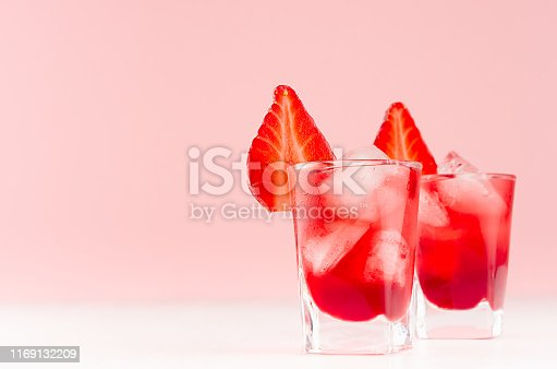 Cold red alcoholic liquors with ice cubes, strawberry slice in two shot glasses on white wood table and pastel pink wall, copy space.