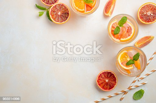 istock Cold refreshing drink with blood orange slices in a glass on a white concrete background. 955514996