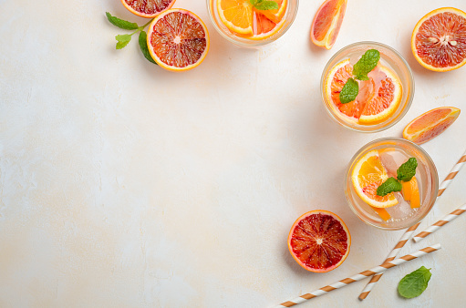 Cold refreshing drink with blood orange slices in a glass on a white concrete background.