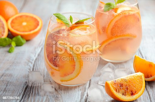 Cold refreshing drink with blood orange slices in a glass on a wooden background. Selective focus, copy space.