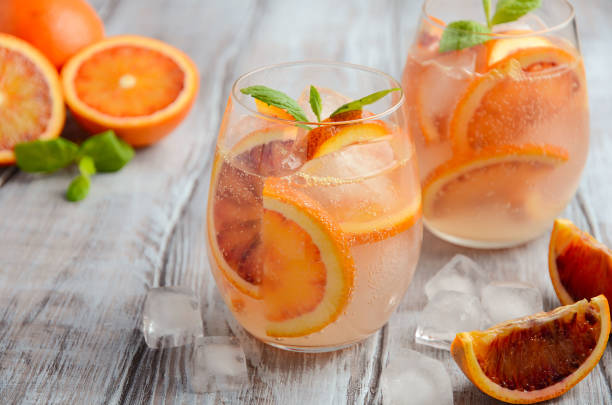 Cold refreshing drink with blood orange slices in a glass on a wooden background stock photo