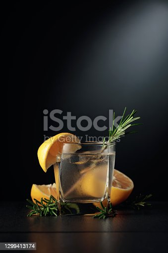 Cold refreshing drink with ice, lemon, and rosemary. The frozen glass with a cocktail gin and tonic on a black background. Copy space.