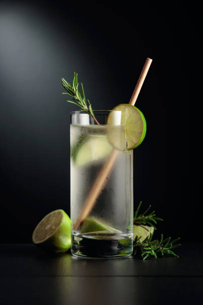 Cold refreshing drink with ice, lime, and rosemary. stock photo