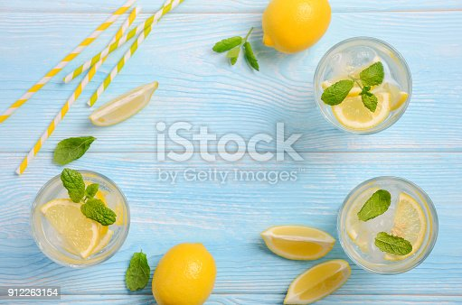 istock Cold refreshing summer drink with lemon and mint on light blue wooden background. 912263154