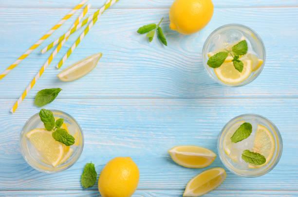 清涼的夏日飲料, 檸檬和薄荷在淡藍色的木制背景下。 - 檸檬水 個照片及圖片檔