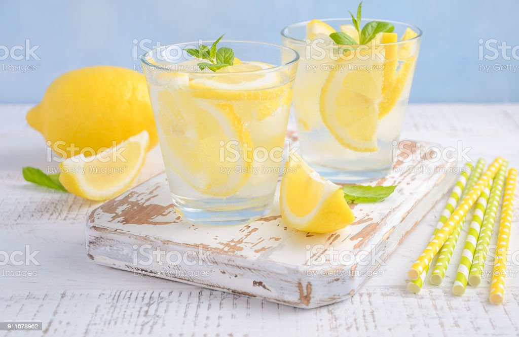 Cold refreshing summer drink with lemon and mint on wooden background.