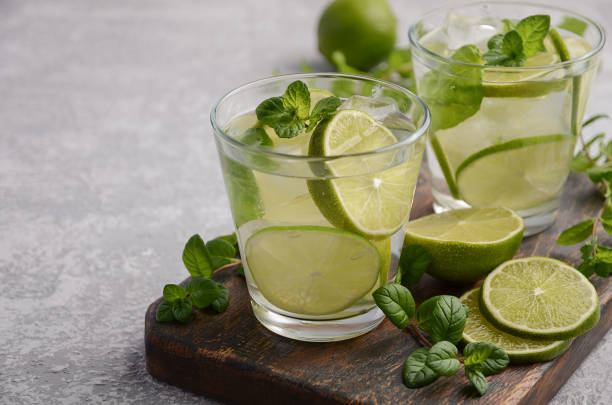 Cold refreshing summer drink with lime and mint in a glass on a grey concrete or stone background. stock photo