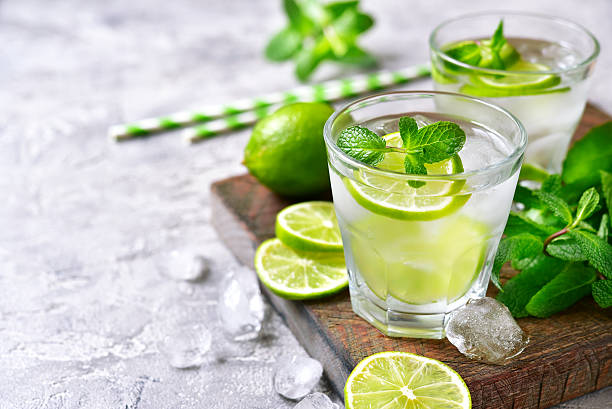 Cold refreshing summer lemonade mojito. Cold refreshing summer lemonade mojito in a glass on a grey concrete or stone background. mojito stock pictures, royalty-free photos & images