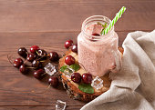 istock Cold refreshing sweet cherry and milk smoothie in a glass jar with straws, scattered berries and ice, linen napkin on a wooden background. 1262992310