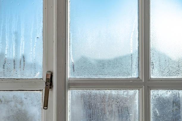 koude kamer interieur met uitzicht op watercondensatie gevormd op interieur ramen tijdens de vroege winter. - luchtvochtigheid stockfoto's en -beelden