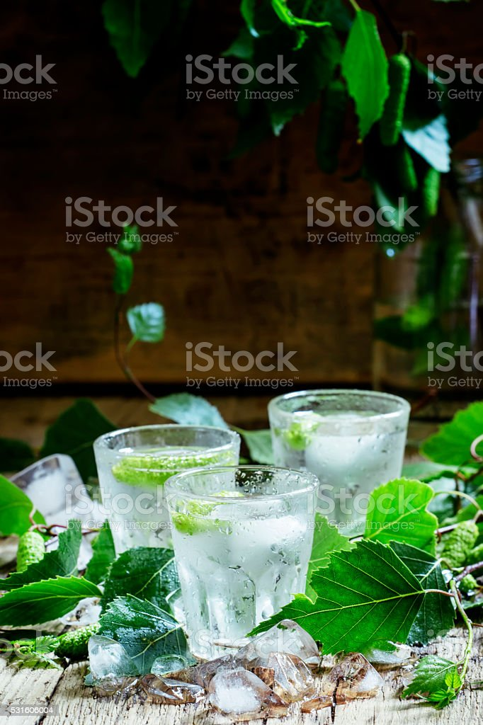 Cold Russian vodka, on birch buds, crushed ice birch leaves foto
