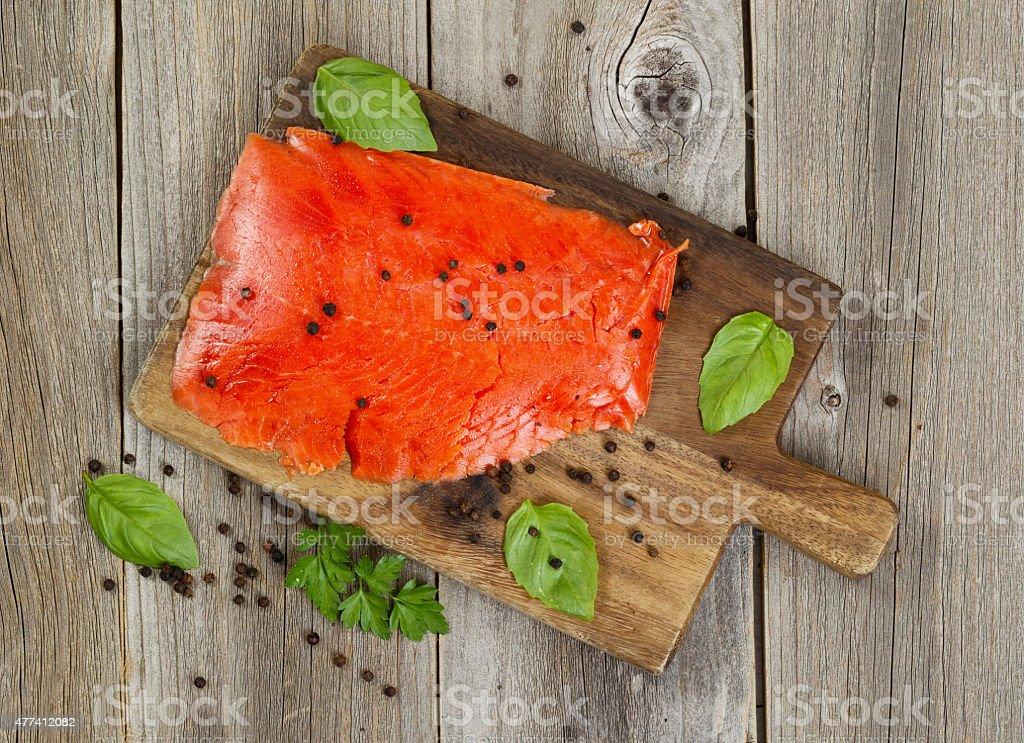Cold smoke red salmon being prepared on wooden server board stock photo