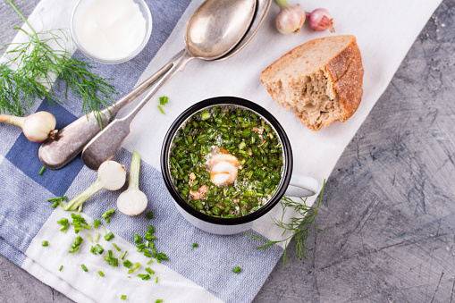 Cold Soup Okroshka in enamel cup and raw ingredients on grey stone table