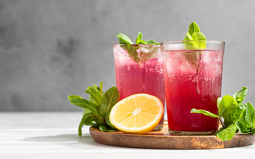 Cold sparkling hibiscus (karkade) tea with lemon, mint and ice in glasses on a grey stone background.