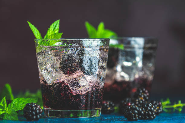 Cold summer berry drink with blackberries. Refreshing summer drink with syrup, blackberry and ice on dark blue concrete background stock photo