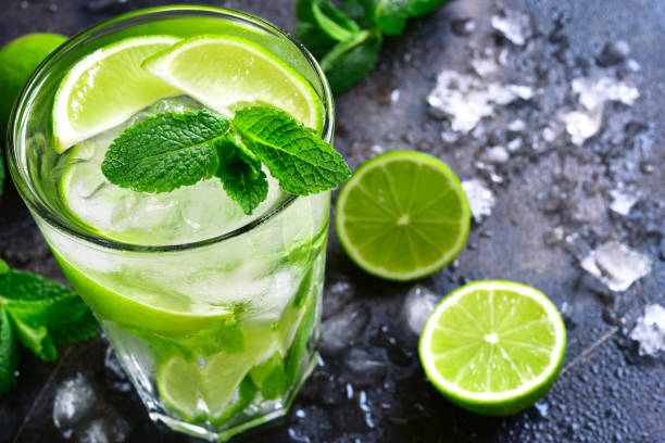 Cold summer drink mojito Cold summer drink mojito in a tall glass on a dark slate,stone or metal background. mojito stock pictures, royalty-free photos & images