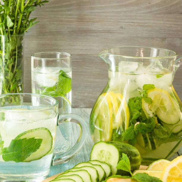 Bebida fria do verão do gengibre, do pepino, da hortelã e do limão em um jarro e em um vidro-Detox fresco. - foto de acervo