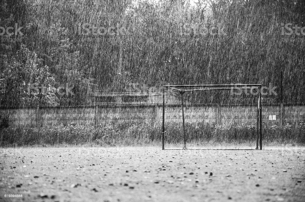 Cold summer rain on empty football field stock photo