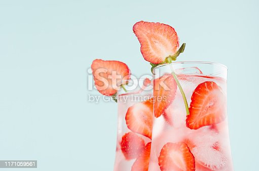 Cold summer strawberry water with strawberry slices, ice cubes, soda in misted glass on pastel green color background, closeup, half, edge, top.