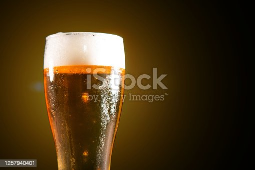 1073474208 istock photo Cold tasty beer on hot summer day. Glass of beer on wooden table on black background 1257940401