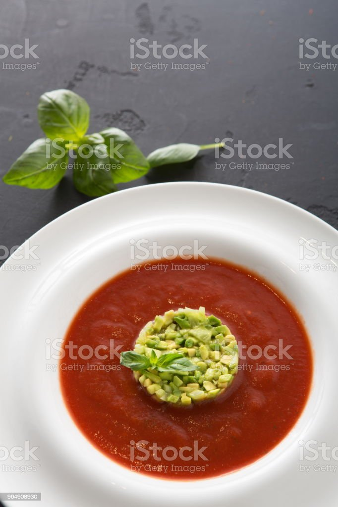 Cold tomato soup gazpacho with avocado close up royalty-free stock photo