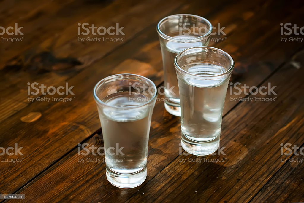 Cold vodka in a glass on a wooden table stock photo