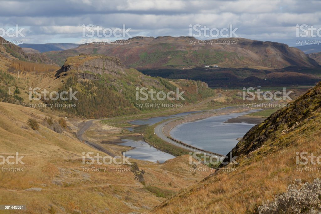 Cold water in Iceland. Waterfall in rocky mountains. Fresh and green grass. Beautiful mountain range in the background. royalty-free stock photo