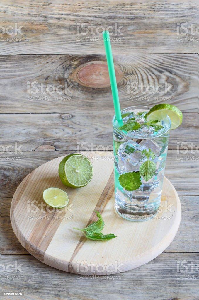 Eau froide avec la vodka, de feuilles de menthe et d'une rondelle de citron vert. Comte - Photo de Agrume libre de droits