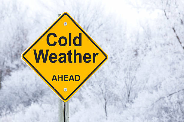 cold weather ahead road warning sign - weather stock photos and pictures