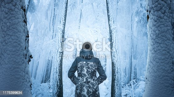 Woman walking through mysterious forest covered with fresh snow and ice crystals.