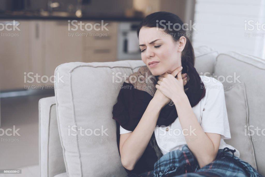 Eine kalte Frau sitzt auf einer hellen Couch eingehüllt in ein blau karierte Peitsche. Sie hält ihre Hände hinter ihrem Hals. – Foto