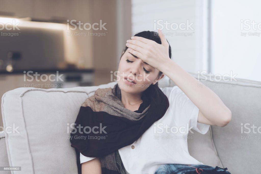 A cold woman sits on a light couch wrapped in a blue checkered whip. She holds her hand to her forehead stock photo