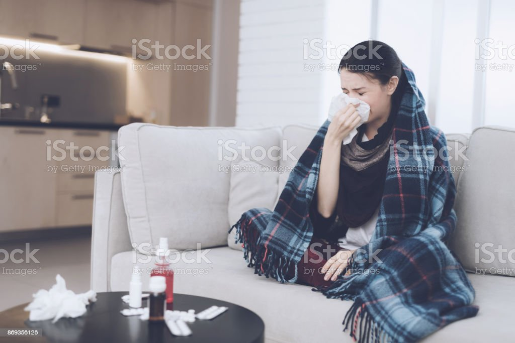A cold woman sits on a light couch wrapped in a blue checkered whip. She blows her nose into a napkin stock photo
