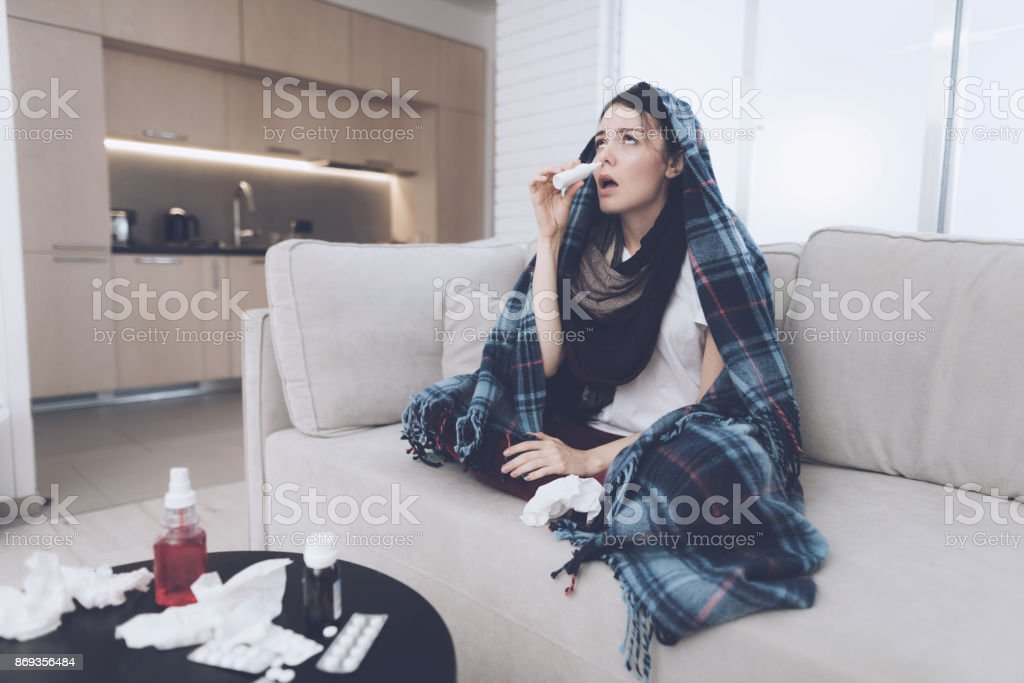 A cold woman sits on a light couch wrapped in a blue checkered whip. She sits plaid over her head stock photo