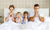 istock colds and viral diseases. family with runny nose and fever in bed 1182706731
