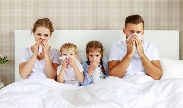 colds and viral diseases. family with runny nose and fever in bed - polmonite virus foto e immagini stock