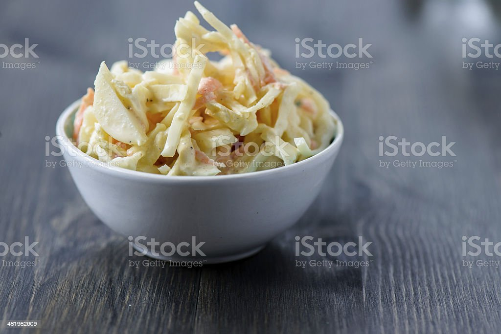 Coleslaw in a bowl on  wooden table stock photo