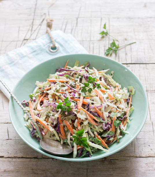 coleslaw of cabbage, carrots and various herbs with mayonnaise in a large plate on a wooden background. - coleslaw stock pictures, royalty-free photos & images