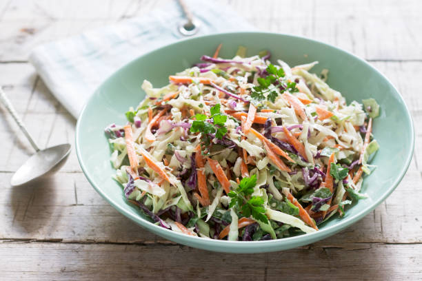 coleslaw of cabbage, carrots and various herbs with mayonnaise in a large plate on a wooden background. - cavolo foto e immagini stock