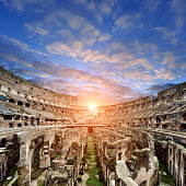 Coliseum at sunset in dramatic sky, Rome, Italy.