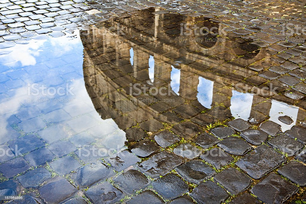 Coliseum reflected in a puddle and cobblestones. Roma Italy stock photo