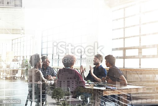 Multiple exposure shot of businesspeople having a meeting superimposed over a cityscape