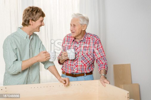 459069877 istock photo Collaboration: Grandfather and grandson assembling furniture 187046556