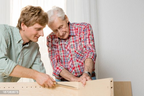 459069877 istock photo Collaboration: Grandfather and grandson assembling furniture 187083873