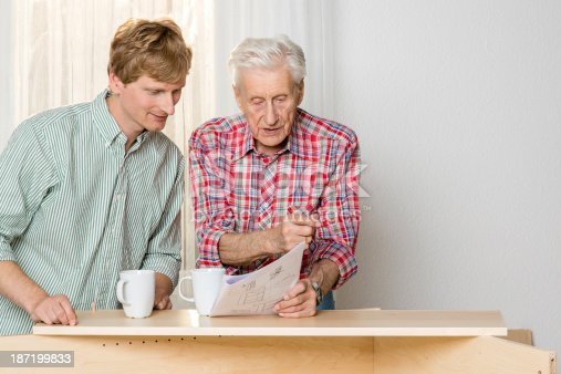 459069877 istock photo Collaboration: Grandfather and grandson assembling furniture 187199833
